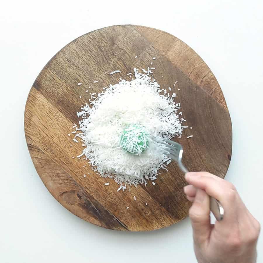 Coating klepon in shredded coconut.