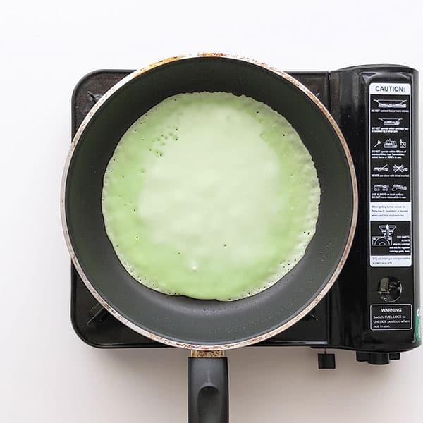 Cooking dadar gulung pancake on a saucepan.