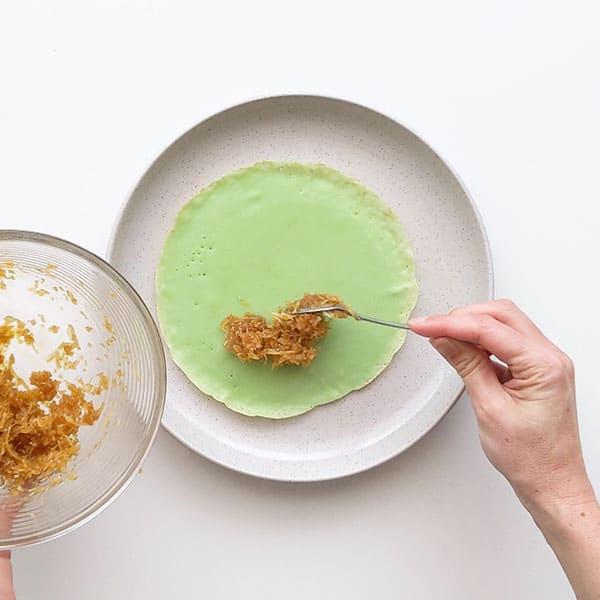 Spooning coconut filling onto pandan pancake.