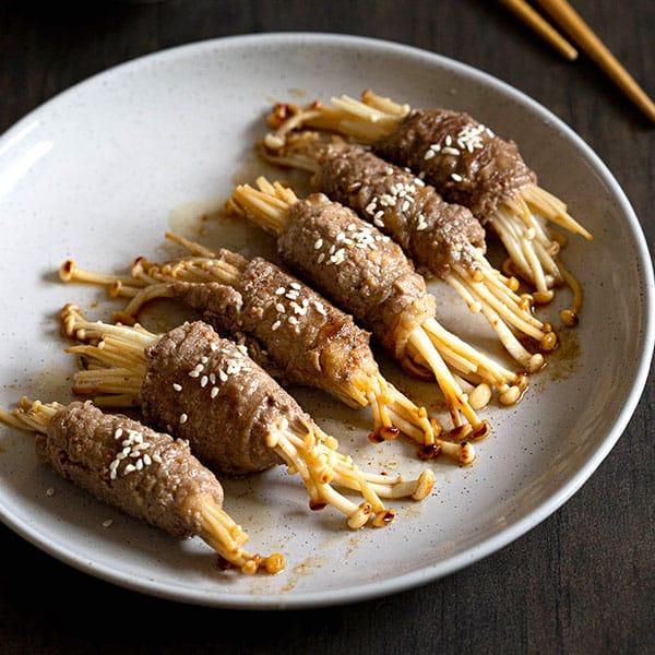 Cooked beef rolls stuffed with enoki mushrooms.