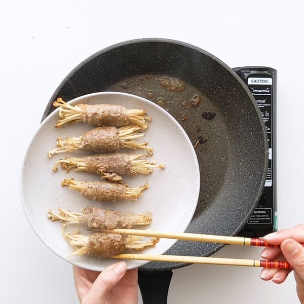 Placing cooked enoki beef rolls on a plate.