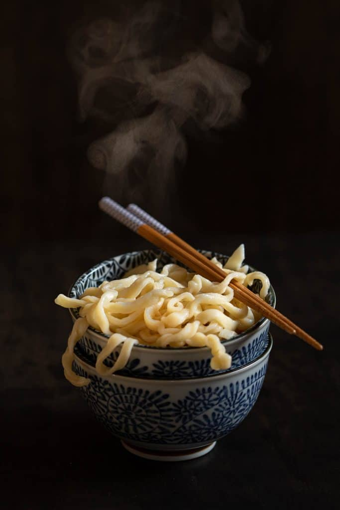 Stack of two blue bowls filled with hot udon noodles and topped with a pair of chopsticks.