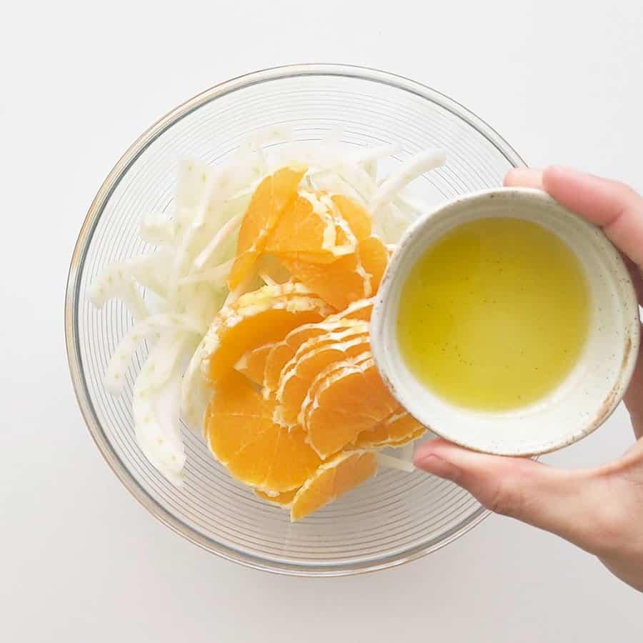 Adding olive oil to fennel and orange slices.
