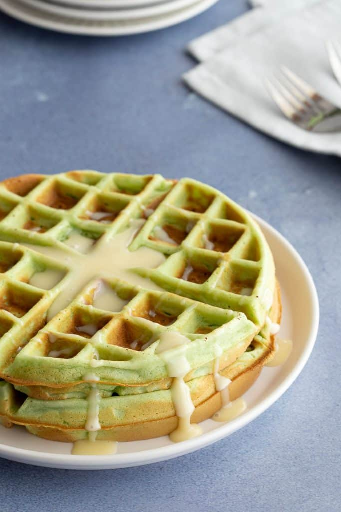 Stack of green waffles drizzled with sweetened condensed milk.