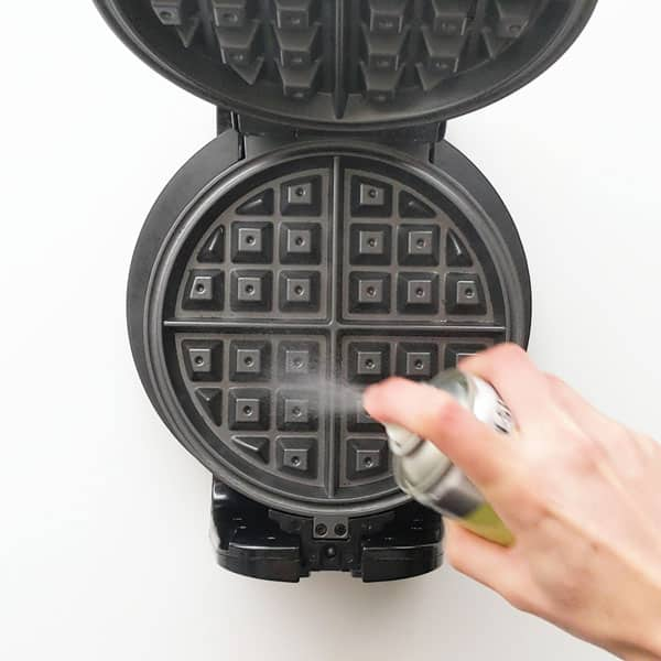 Spraying cooking oil onto waffle iron.