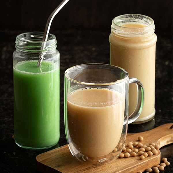Three glasses of soy milk, with soy beans.