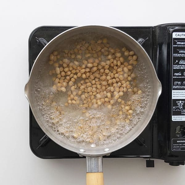 Boiling soy beans in pan.