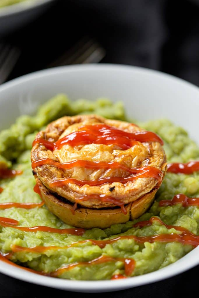 A deliciously flaky beef pie sitting on top of a bed of mushy pea soup, drizzled with tomato sauce.