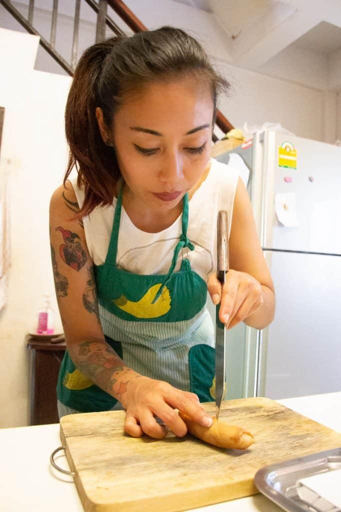Thai chef cutting spring rolls.