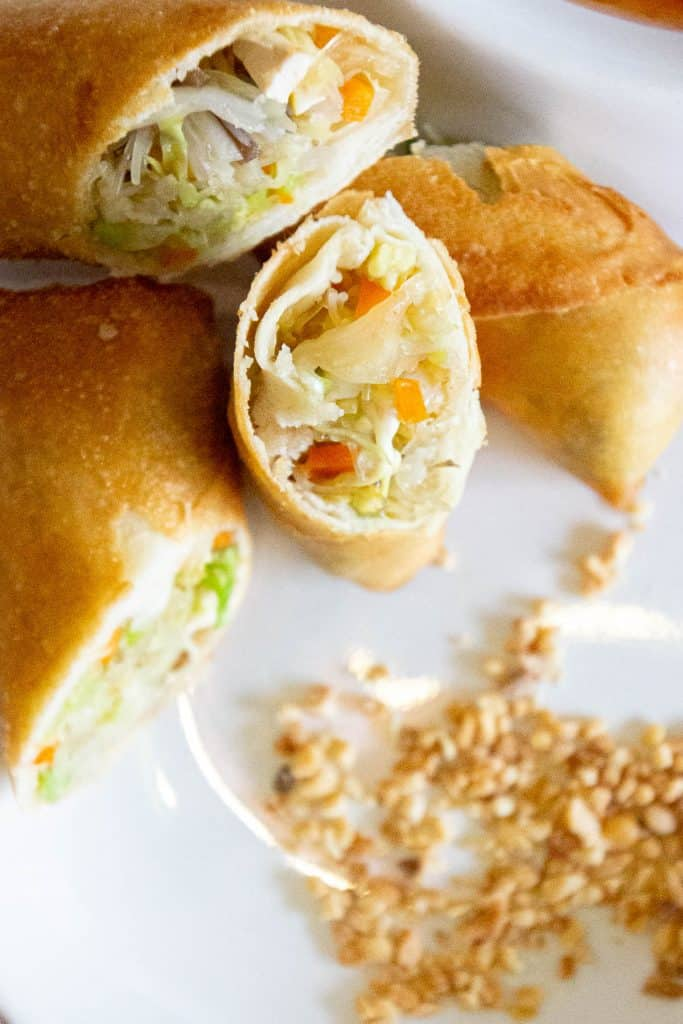 Fried spring rolls on a white plate with crushed peanuts.