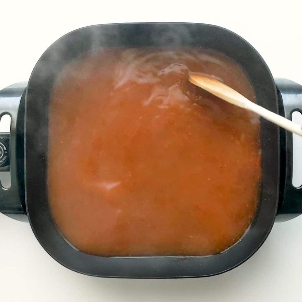 Preparing the tteokbokki stock in an electric frypan.