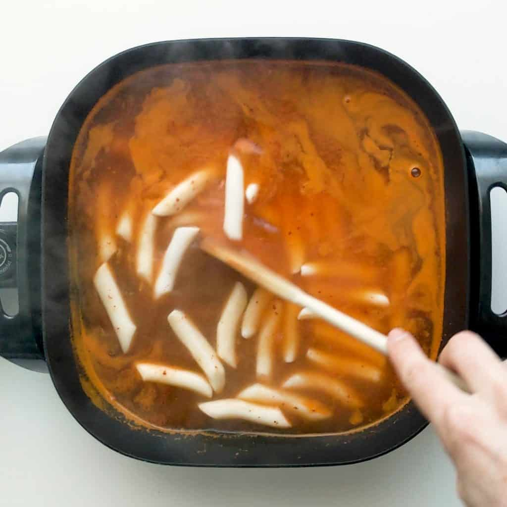 Cooking rice cakes in tteokbokki sauce.
