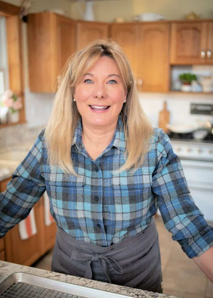Lisa Steele in a check blue shirt in the kitchen.