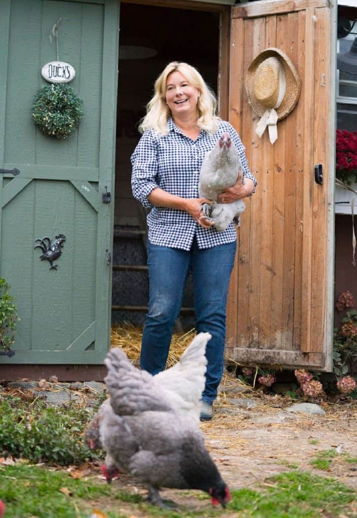 Lisa Steele with her chickens outside coop.