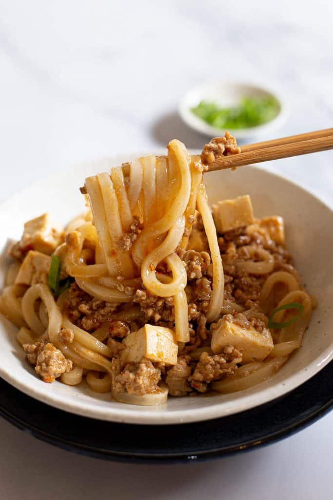 Holding udon noodles with chopsticks.
