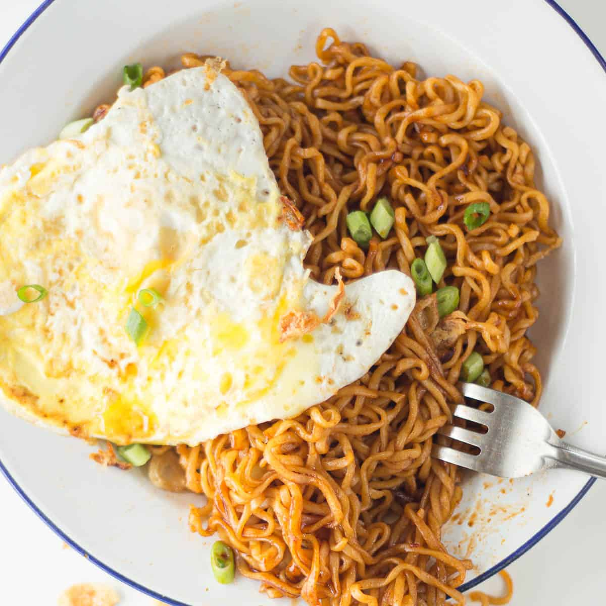 Pile of mie goreng noodles on a plate with a fried egg.