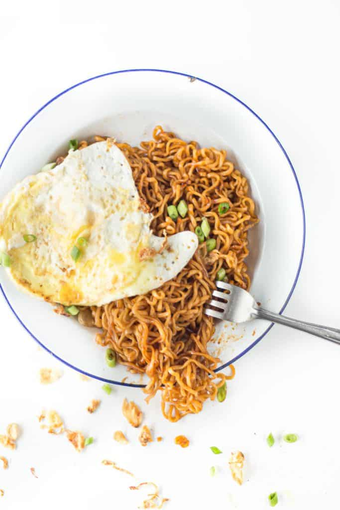 Plate of noodles topped with a fried egg, Malaysian style.