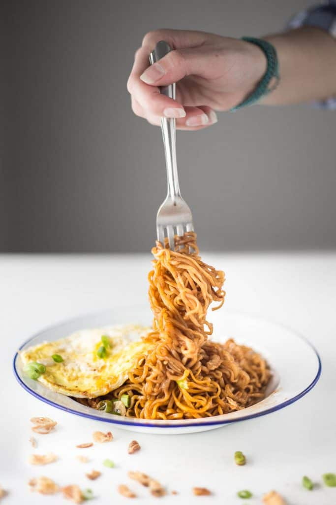 Twirling instant noodles around a fork.