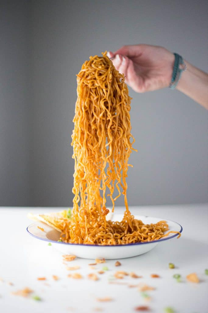 Noodles covered in a mee goreng sauce base being lifted out of the bowl.