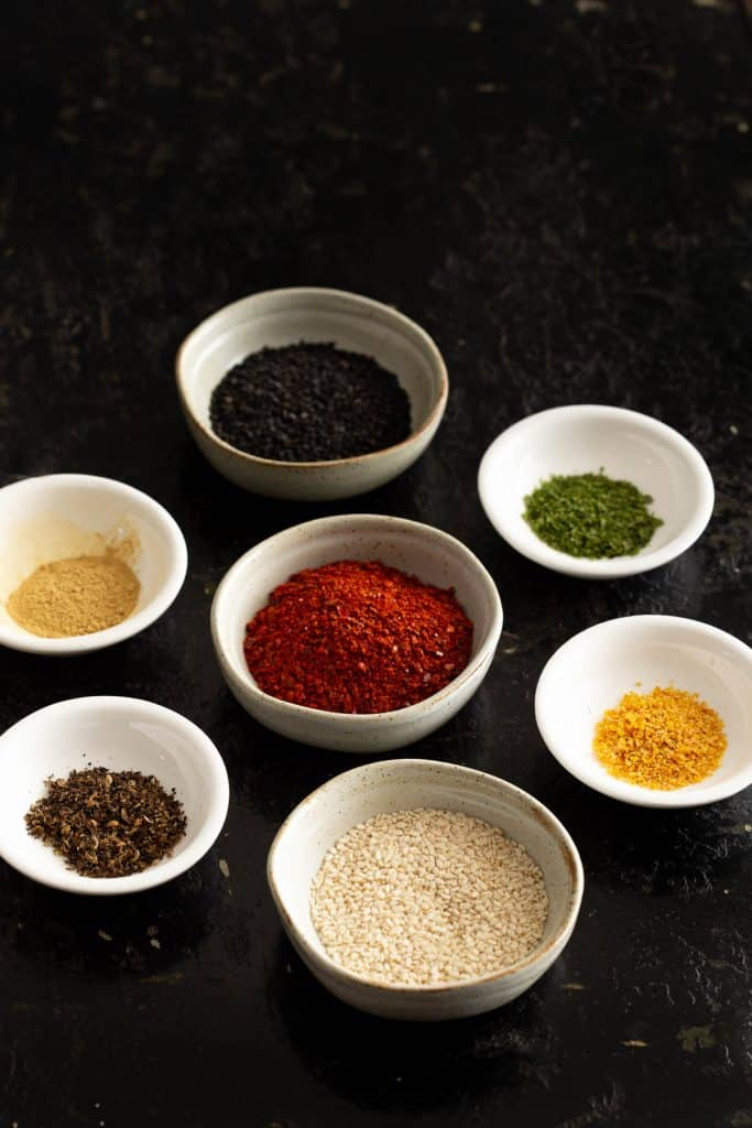 Seven spices in white dishes.