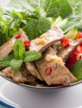 A bowl of Thai beef salad garnished with fresh chilli.