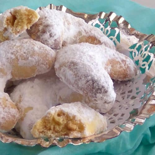 A glass dish filled with Greek Christmas biscuits sprinkled with icing sugar.