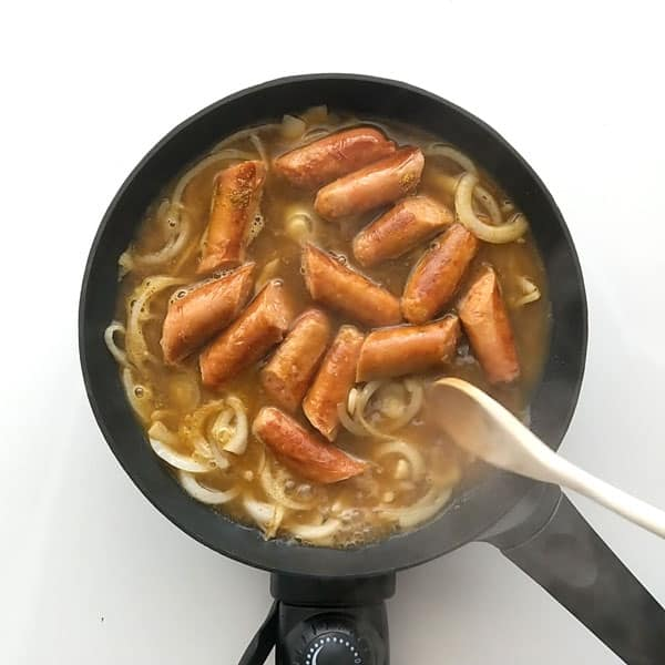 Simmering onions and sausages in curry gravy.