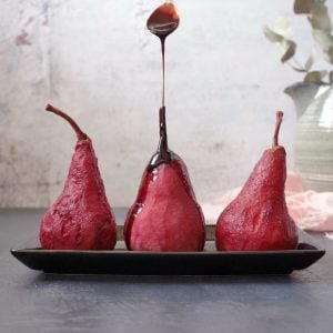 Drizzling sauce over red wine poached pears.