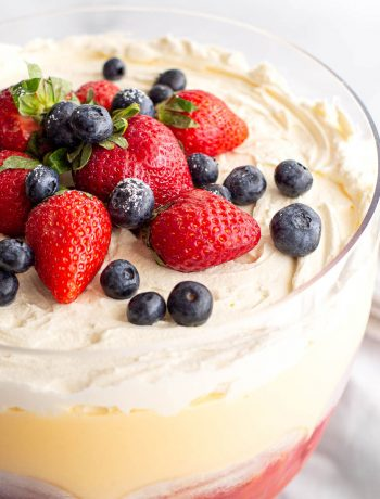 Strawberries and blueberries topped on a custard trifle.