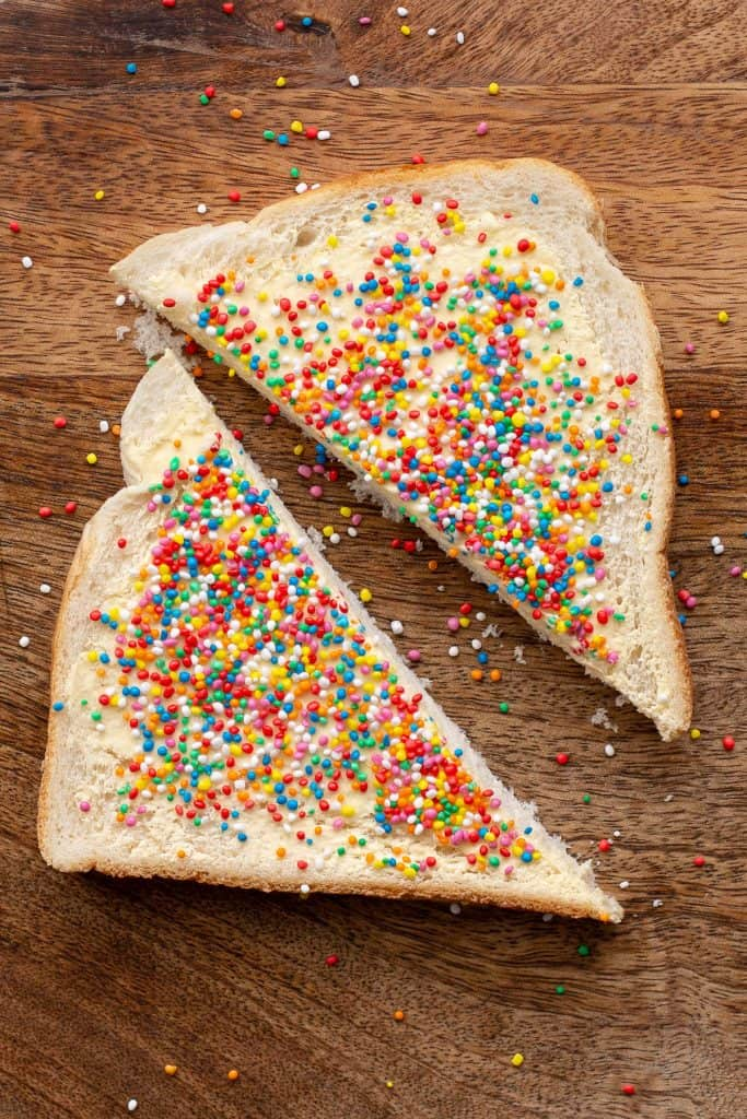 A piece of white bread topped with sprinkles, sliced in half to make two triangles.