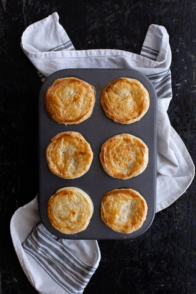 Six freshly baked party pies in a muffin tray.