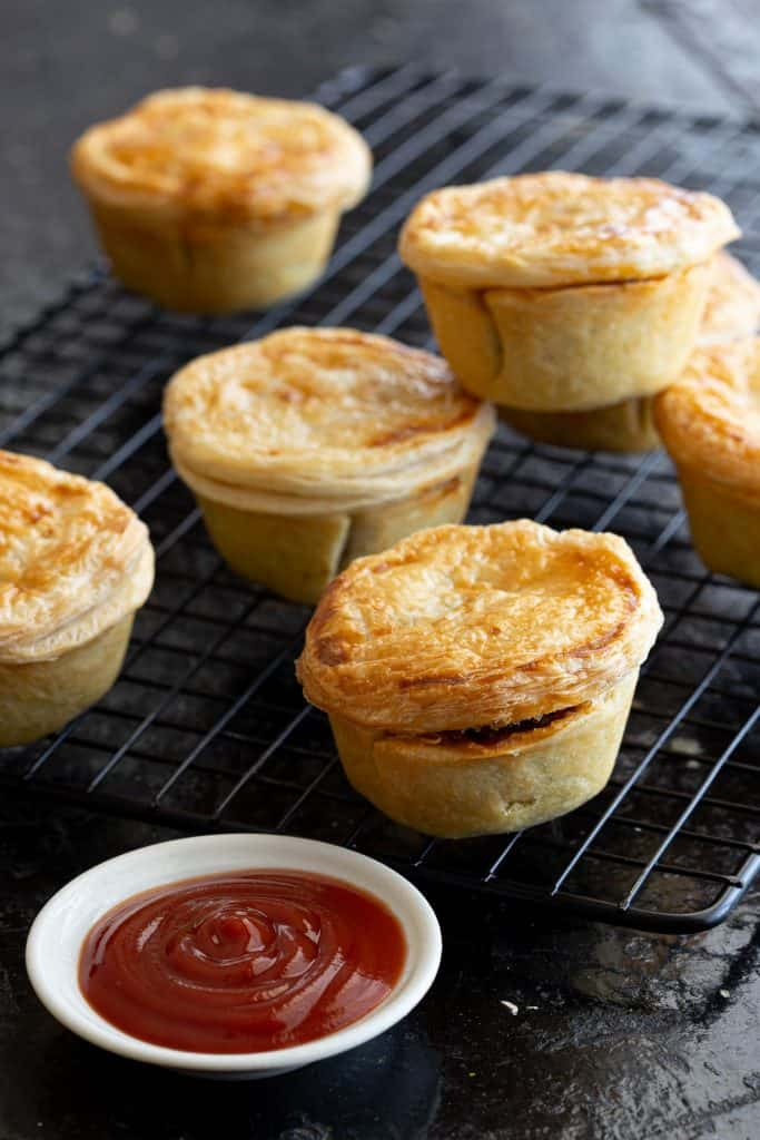 Beef party pies on a cooling rack with tomato dipping sauce.