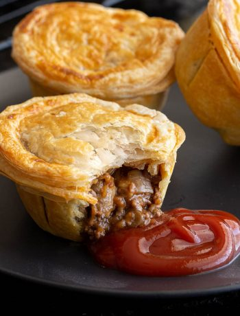 Beef pie on a plate with tomato sauce and more pies in the background.