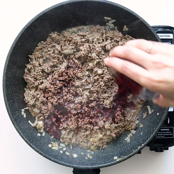 Pouring red wine into the meat filling.