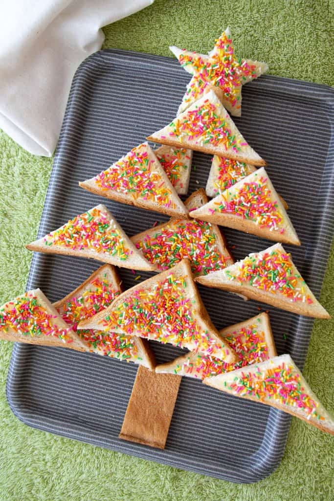 Pieces of fairy bread on a platter made to look like a Christmas tree.