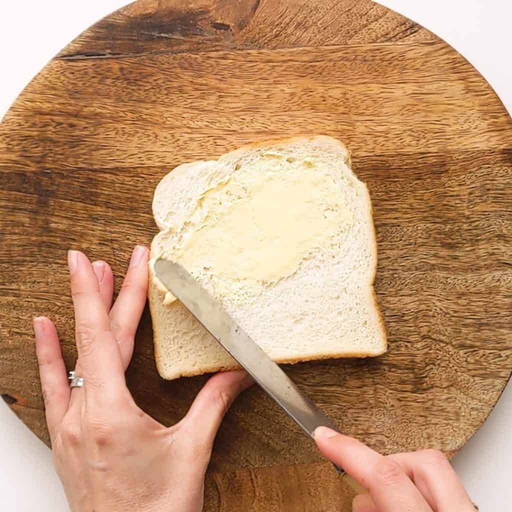 Spreading butter over a slice of white bread.