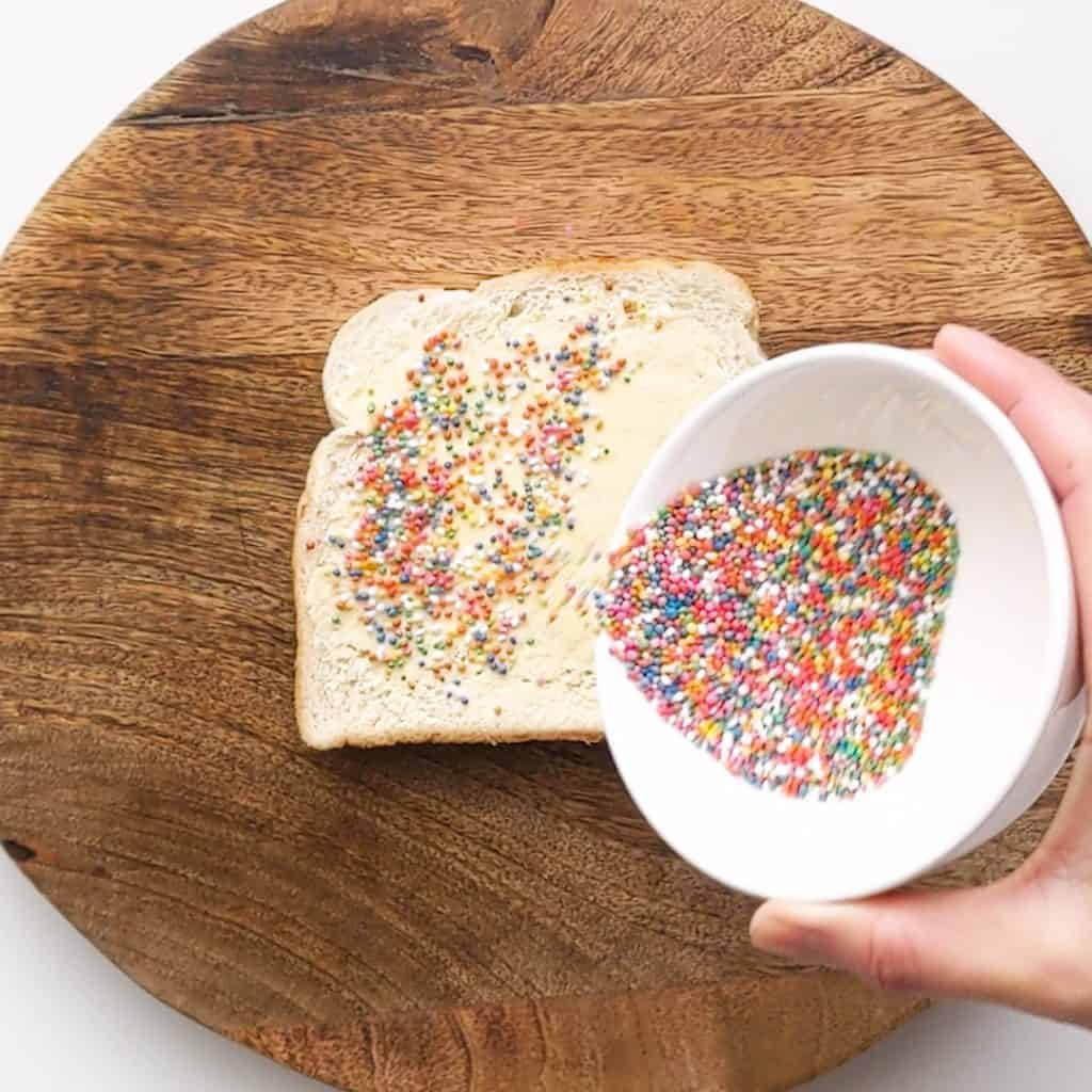 Pouring sprinkles onto buttered bread.