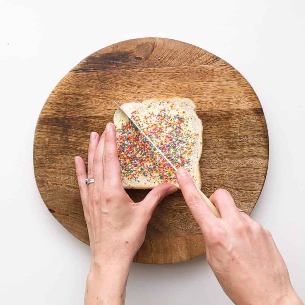 Slicing a piece of fairy bread in half to make two triangles.