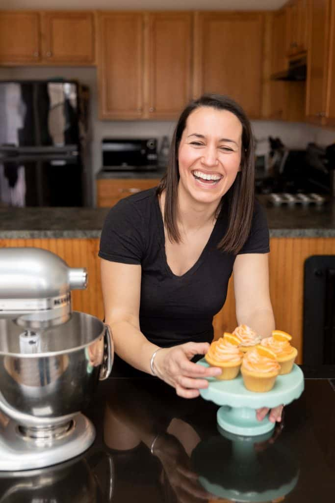 Lynn laughing with cupcakes while cooking.