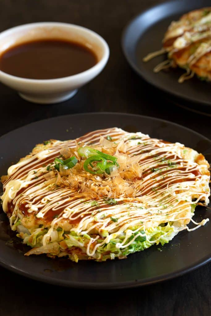Japanese okonomiyaki pancake with katsuoboshi and aonori on top.