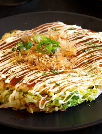 Okonomiyaki topped with sauce, kewpie mayonnaise, bonito flakes and seaweed flakes.