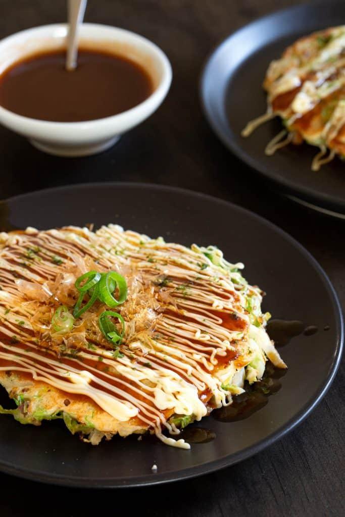 Two Japanese pancakes with homemade okonomiyaki sauce in the background.