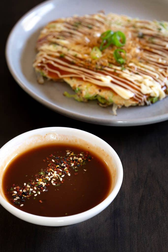 Okonomiyaki sauce with Japanese pancake in the background.