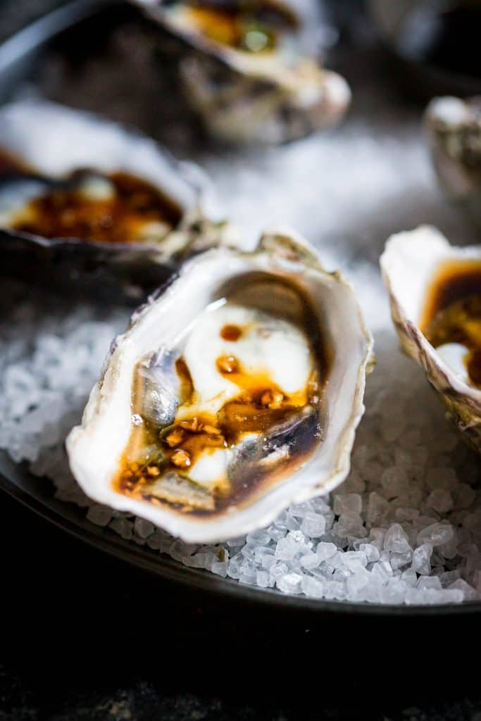 Close up shot of fresh oyster in its shell, topped with soy sauce and fresh garlic.
