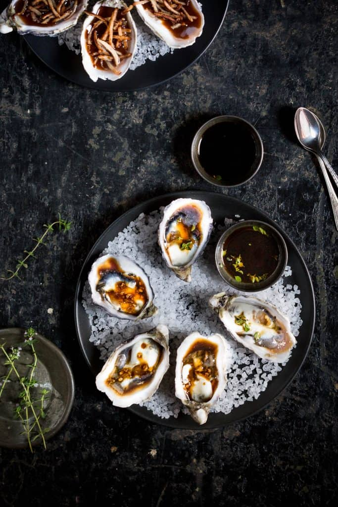 Top down view of oysters on a bed of rock salt, with ponzu dipping sauce.