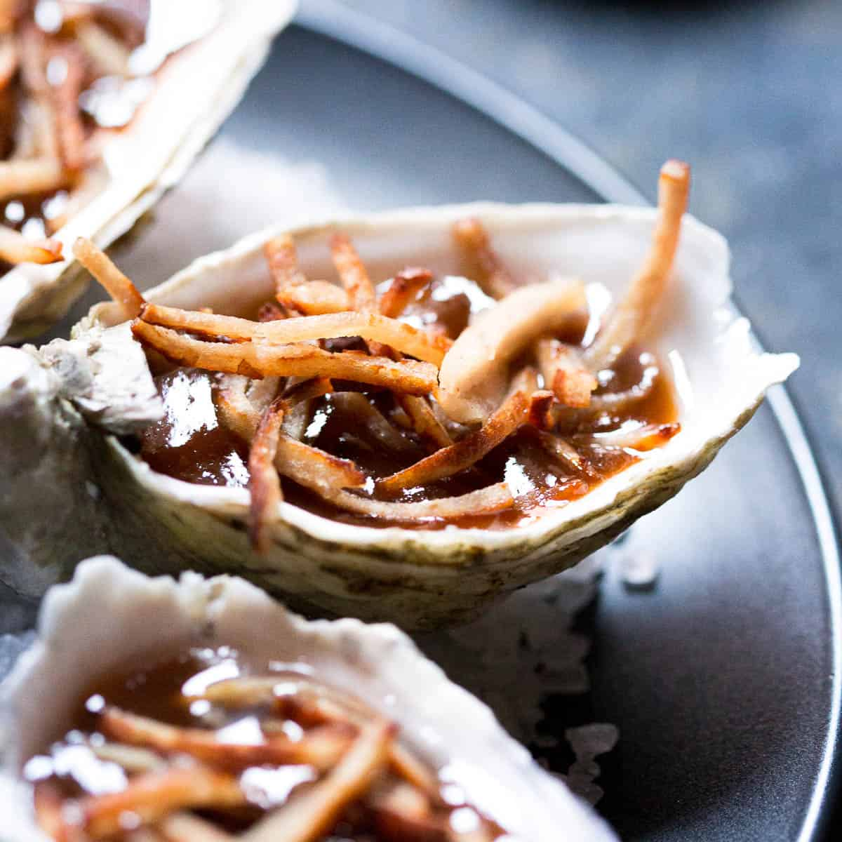 Close up shot of oyster in kilpatrick sauce with bacon.