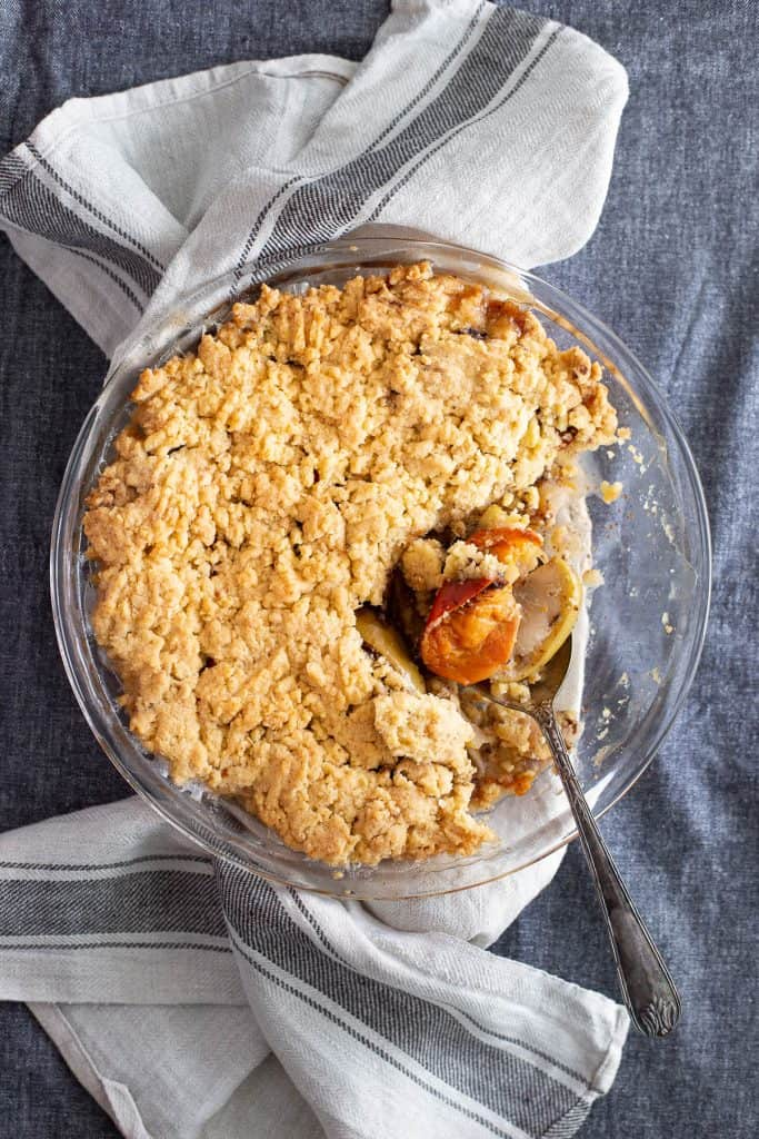 Top down view of persimmon crumble showing a spoon scooping out some of the baked filling.
