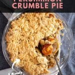 Freshly baked apple persimmon crumble pie in a glass dish, with a spoon scooping out the filling.
