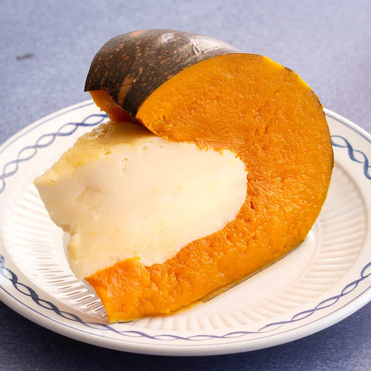Pumpkin filled with coconut custard on a white plate.