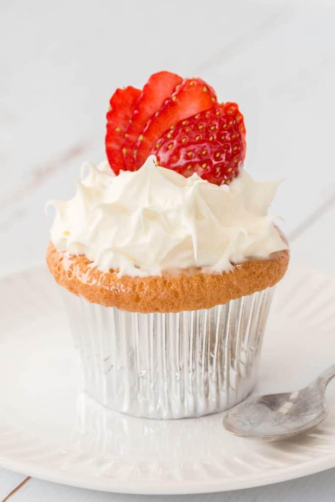 A tres leches cupcake on a plate, topped with whipped cream and strawberry slices.